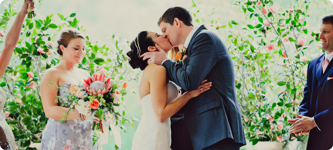 wedding ceremony kiss with gorgeous wedding florals
